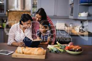 Multi-generation family sitting together in kitchen