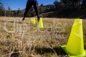 Low-section of woman running through training cones