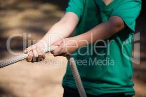 Boy practicing tug of war during obstacle course training in the boot camp