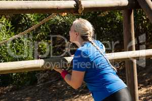 Woman exercising on outdoor equipment during obstacle course training