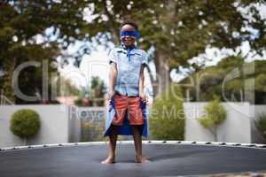 Boy in superhero costume standing on trampoline