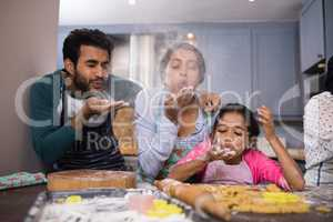 Playful family blowing flour in kitchen