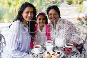 Portrait of smiling multi-generation family sitting together by breakfast table