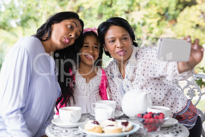 Multi-generation family taking selfie while sitting together by breakfast table