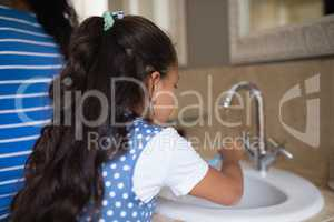 Girl with mother brushing teeth at bathroom sink