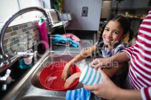 Portrait of cute girl helping her mother in kitchen