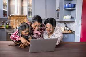 Happy multi-generation family using laptop in kitchen