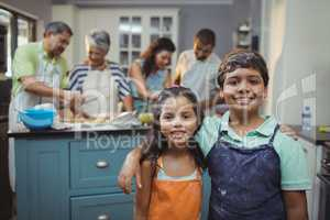 Siblings smiling at camera while family members preparing dessert in background