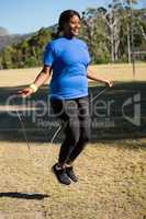 Fit woman skipping rope in the park