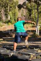 Boy running over tyres during obstacle course training