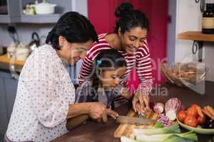 Multi-generation family preparing food together in kitchen