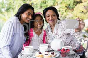 Smiling multi-generation family taking selfie while sitting by breakfast table