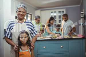 Grandmother and granddaughter smiling at camera while family members preparing dessert in background