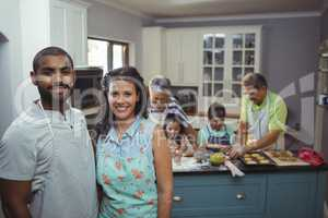 Couple smiling at camera while family members preparing dessert in background