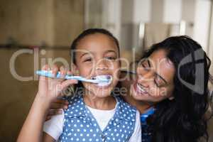 Portrait of girl brushing teeth with mother in bathroom