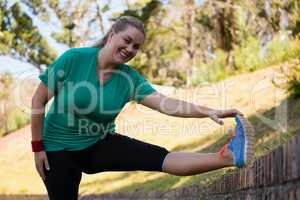 Woman performing stretching exercise during obstacle course training