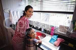 Portrait of smiling girl helping her mother in kitchen
