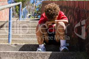Upset boy sitting on staircase in the boot camp