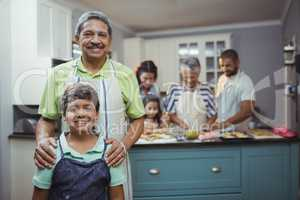Grandfather and grandson smiling at camera while family members preparing dessert in background
