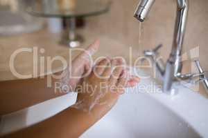 Hand of girl washing hands at bathroom sink