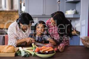 Portrait of girl preparing food with mother and grandmother in kitchen