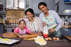 Smiling multi-generation family preparing food in kitchen