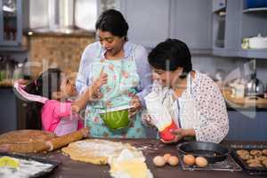 Happy multi-generation family preparing food