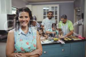 Woman smiling at camera while family members preparing dessert in background