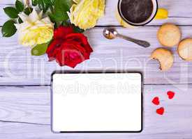 Tablet with white screen, cup of black coffee and bouquet of ros