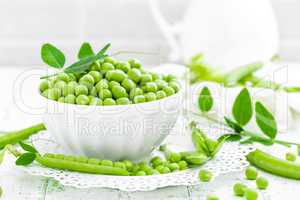 Green peas with leaves on white background