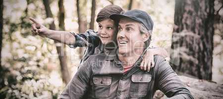Curious boy showing something to father in forest