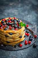 Pancakes with fresh berries and maple syrup on dark background, closeup