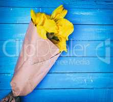 yellow irises wrapped in brown kraft paper