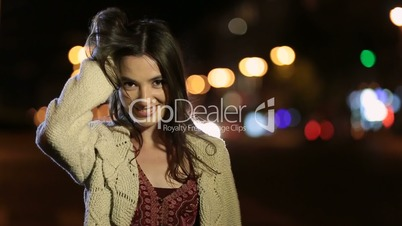 Sexy smiling girl playing with her hair at night