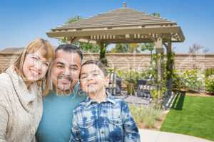 Mixed Race Family In Back Yard Near Patio Cover.