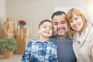 Mixed Race Family In Empty Room With Moving Boxes and Plants.