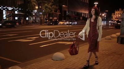 Positive fashionable woman walking on night street