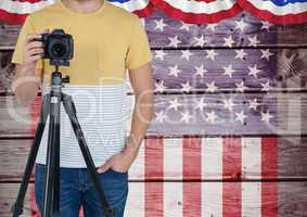 Part of a photographer standing on an american flag background