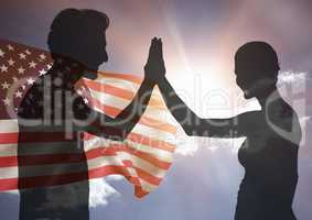 Shadow of people high fiving against american flag and sun