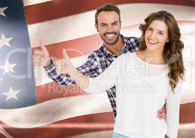 Couple thumbs up  against american flag