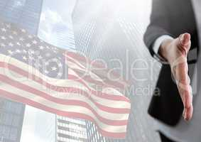 Part of a woman offering her hand against fluttering american flag and buildings