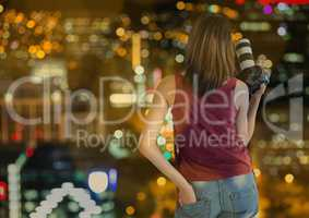 back of photographer with camera on hand in the city at night with blurred lights and bokeh overlap