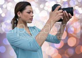 young photographer taking a photo. Blue, orange and white bokeh background
