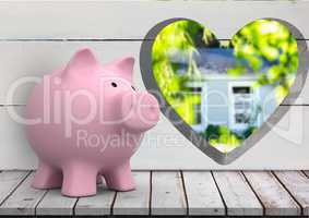 pink piggy bank in front of wood wall with heart hole where we can see a house (blurred)