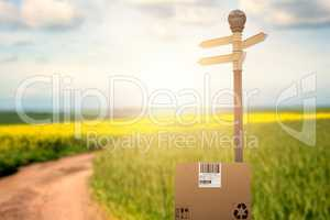 Composite image of cardboard box with road sign