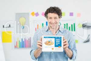 Businessman showing digital 3d tablet with blank screen in creative office
