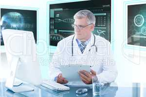 Composite 3d image of male doctor holding clipboard while looking at computer monitor