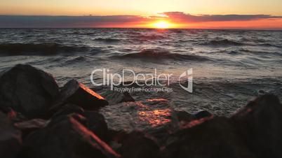 Red sky over a rocky seashore. Sunset landscape.