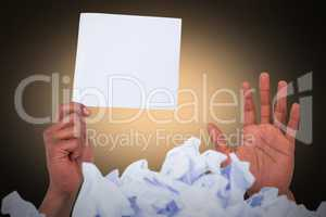 Composite image of heap of crumpled paper with hand holding blank page