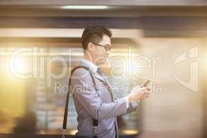 Businessman using smartphone at subway station.